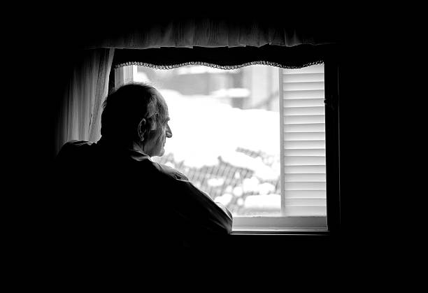 Lonely senior man looking at the window stock photo