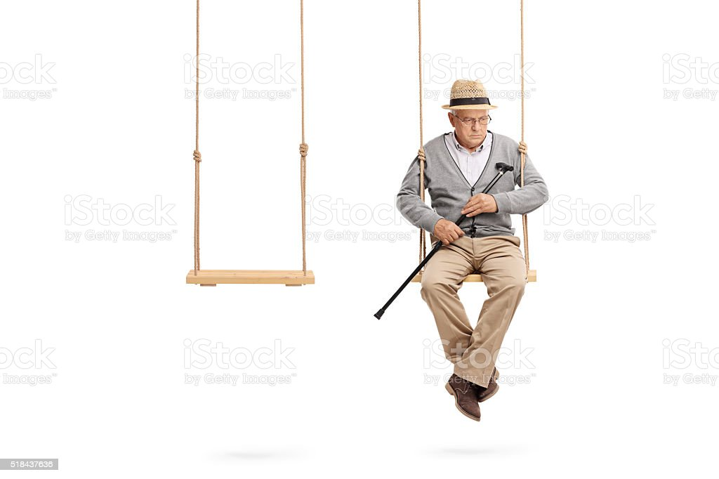 Lonely senior sitting on a wooden swing stock photo