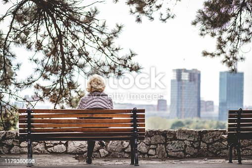 Lonely senior woman is sitting on a bench in a public park. She is looking at distance