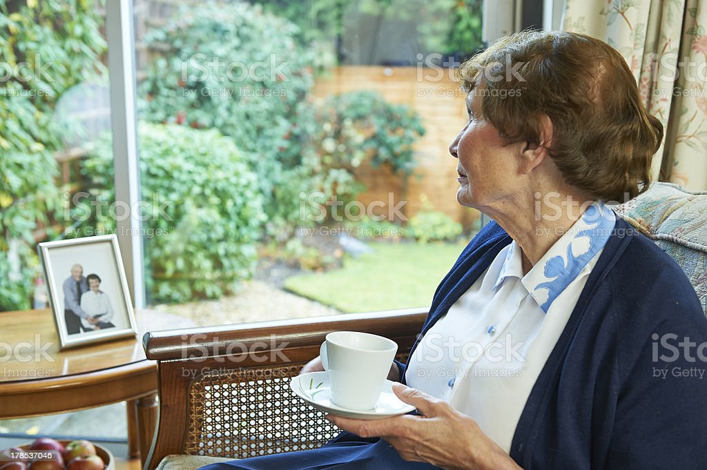 lonely senior woman looking out of window stock photo