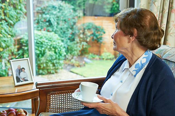 solitude senior femme regardant par la fenêtre - veuve photos et images de collection