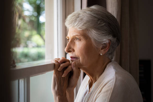 Lonely senior woman Depressed senior woman at home feeling sad. Elderly woman looks sadly outside the window. Depressed lonely lady standing alone and looking through the window. desolation stock pictures, royalty-free photos & images