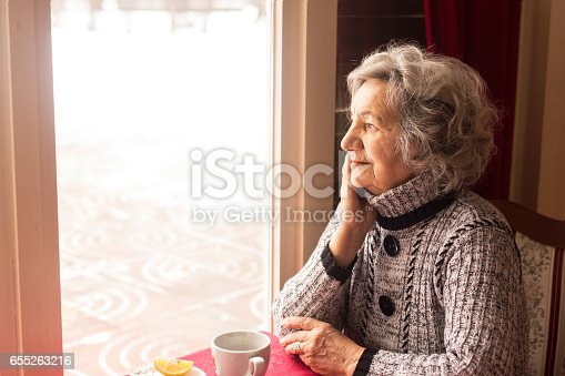 Lonely senior woman looking through window