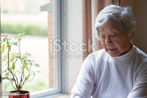 istock Lonely, Senior Woman Sitting by Window with Eyes Closed 972500960