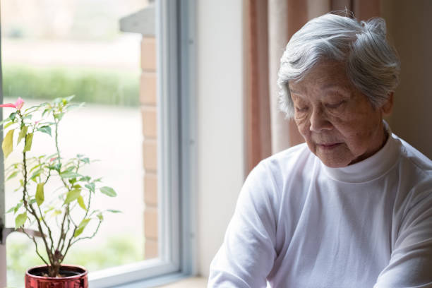 Lonely, Senior Woman Sitting by Window with Eyes Closed stock photo