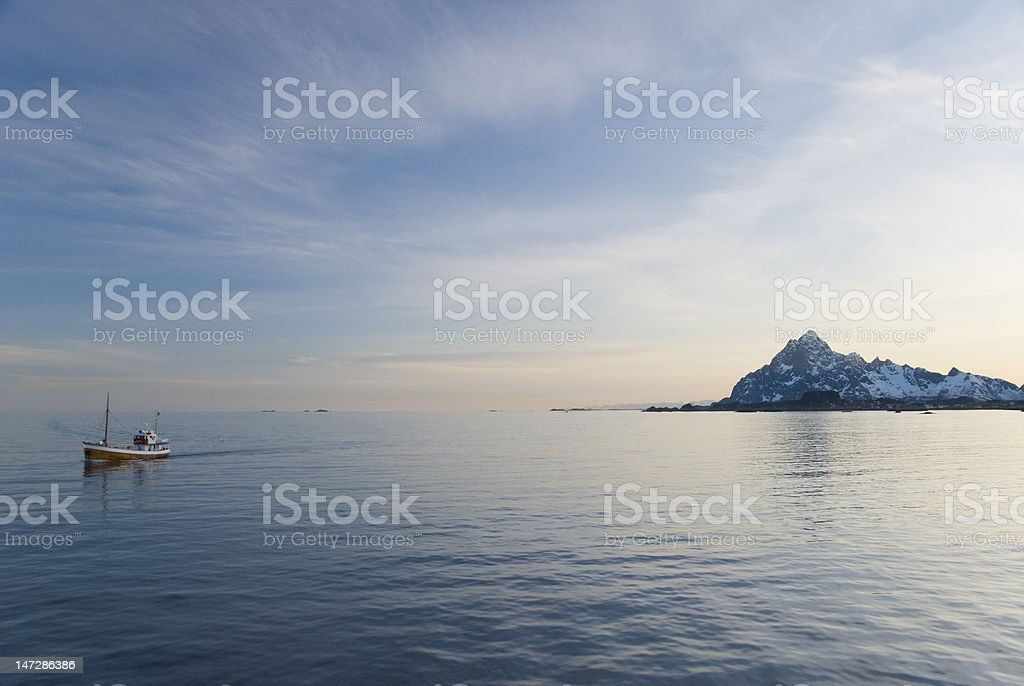 Lonely ship leaving mountains behind at sunset royalty-free stock photo