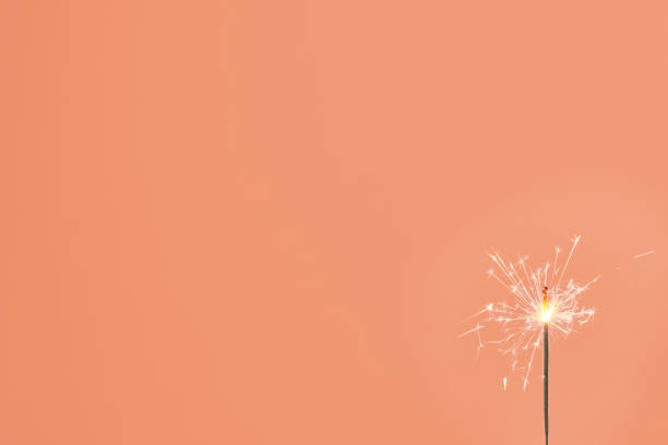 A lonely sparkler stick A lonely sparkler stick against the orange background. Celebration, holiday, birthday, anniversary, new year, Christmas concepts muziekfestival stock pictures, royalty-free photos & images