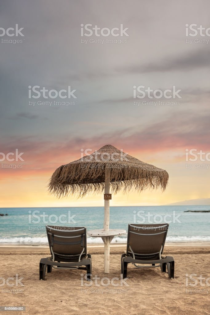 Lonely sunbeds and umbrella with view of stunning sunset - Tenerife, Canary Islands. stock photo