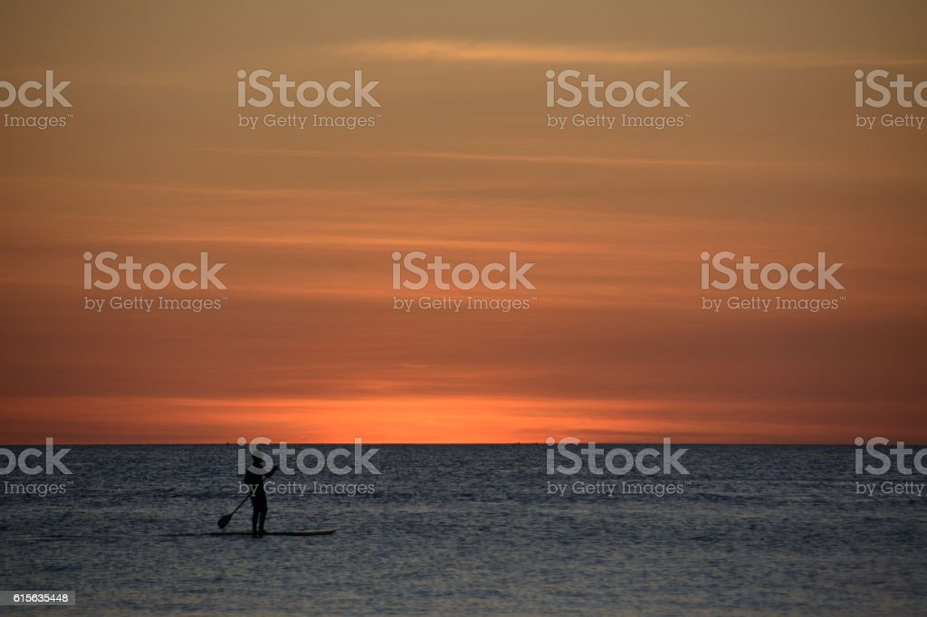Lonely surfer at sunset over the sea, Boracay Philippines stock photo