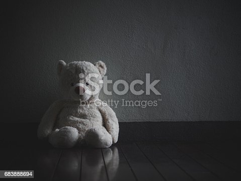 istock Lonely Teddy Bear Sitting in the dark room (Concept about love) 683888694