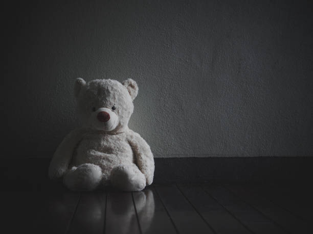 Lonely Teddy Bear Sitting in the dark room (Concept about love) Lonely Teddy Bear Sitting in the dark room (Concept about love) derelict stock pictures, royalty-free photos & images