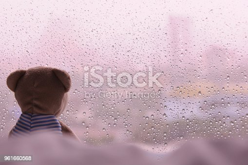 Lonely Teddy Bear sitting on bed and looking out at the window in rainy day. This photo has space background for text.