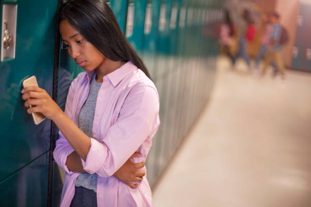 Lonely teenage Asian female student leaning on locker with smart phone in school stock photo