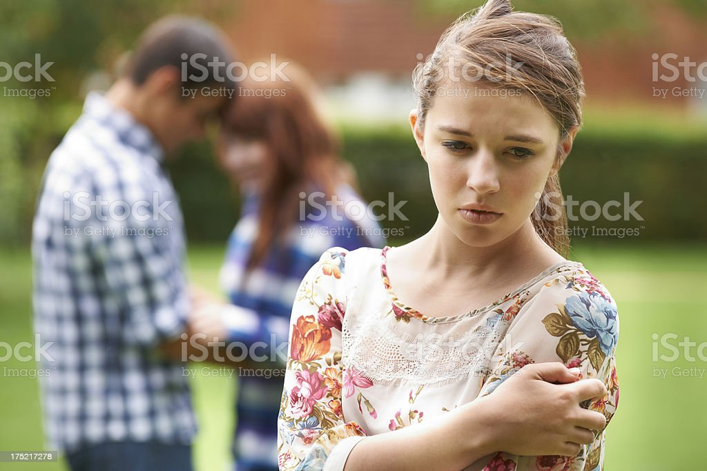 Lonely Teenage Girl Jealous Of Couple In Background stock photo