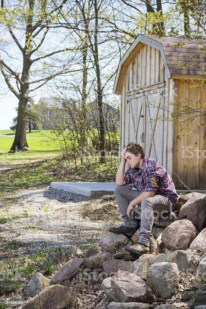 Lonely teenager sitting on a farm in the countryside. royalty-free stock photo