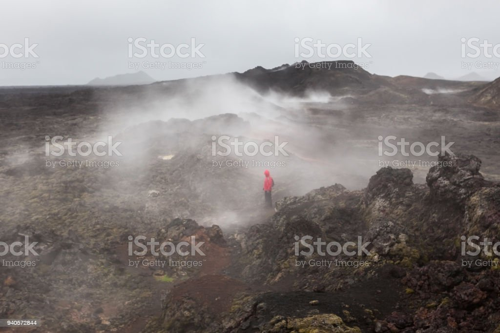 Lonely tourist lost in ashes and smokes of lava field in Krafla volcanic area, Iceland. stock photo