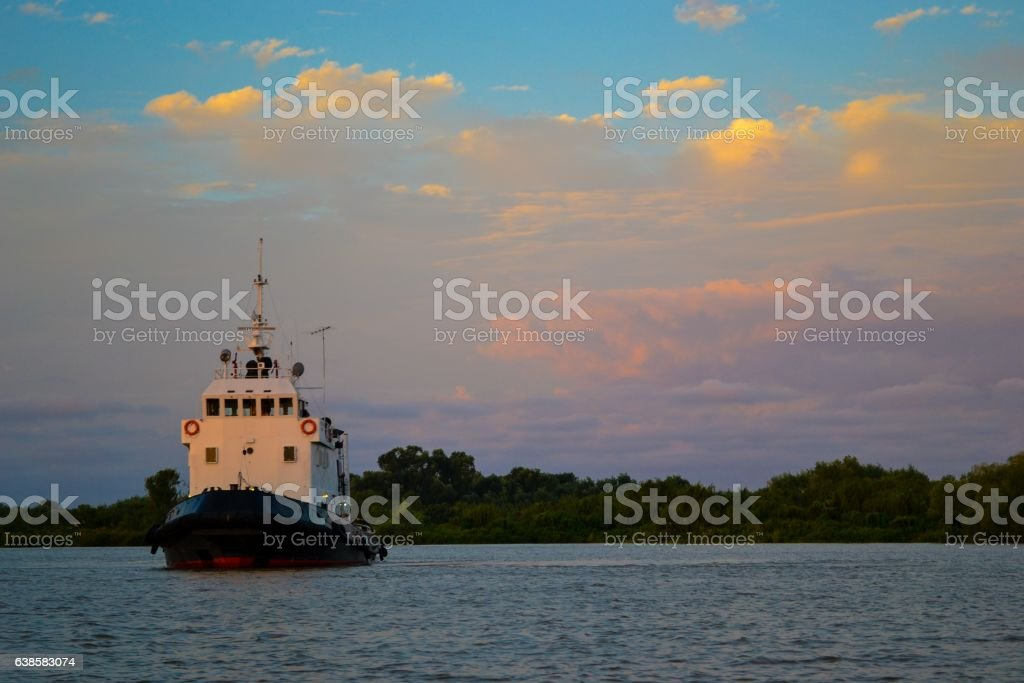 Lonely tug boat at sunset stock photo