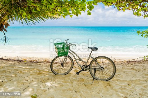 Lonely vintage bicycle on the tropical  sandy beach by a palm tree with sky and calm sea at background.