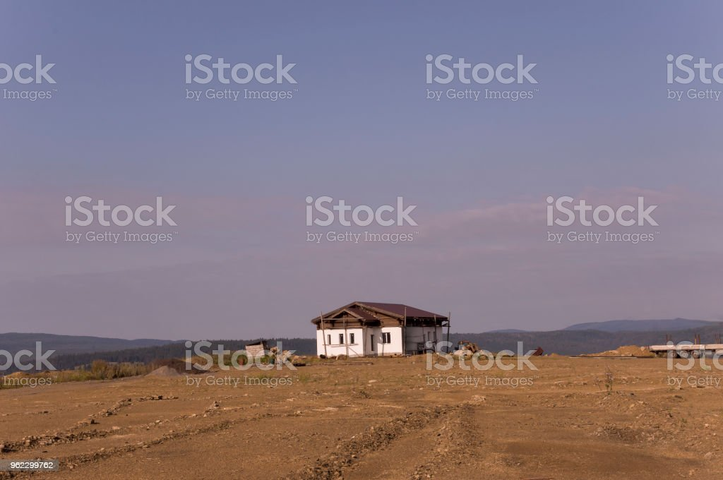 Lonely white forgotten building on the sand mountain. Deep calm blue sky with tints of purple. Ural landscapes. Brown colors. Like a desert stock photo