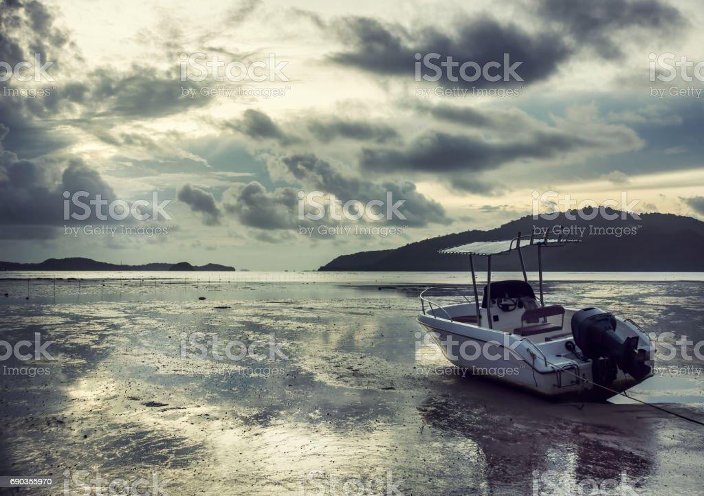 Lonely white motor boat aground in Andaman sea on sunrise stock photo