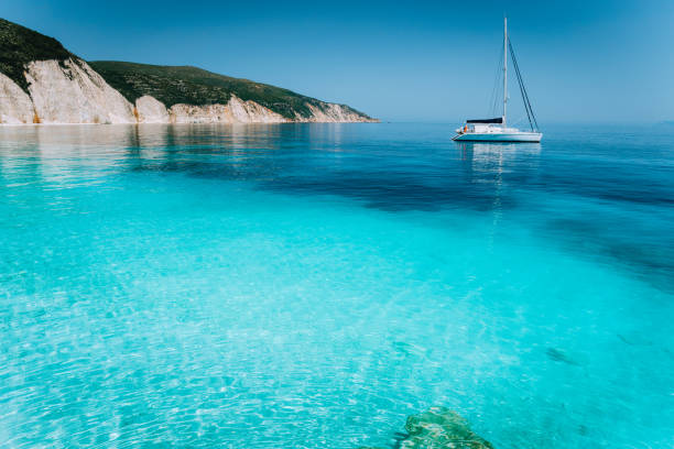 solitario catamarano a vela bianca alla deriva sulla tranquilla superficie del mare. pura acqua di baia azzurra poco profonda di una bellissima spiaggia. paesaggio panoramico della costa rocciosa sullo sfondo - sardegna foto e immagini stock