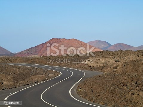 Lonely winding road through the lava fields on Lanzarote island, Spain