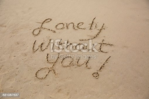 Lonely with you, a message written in the sand at the beach.