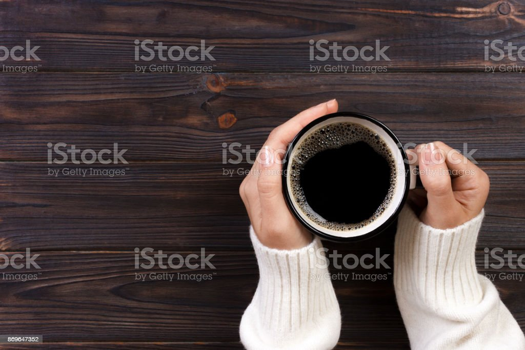 Lonely woman drinking coffee in the morning, top view of female hands holding cup of hot beverage on wooden desk royalty-free stock photo