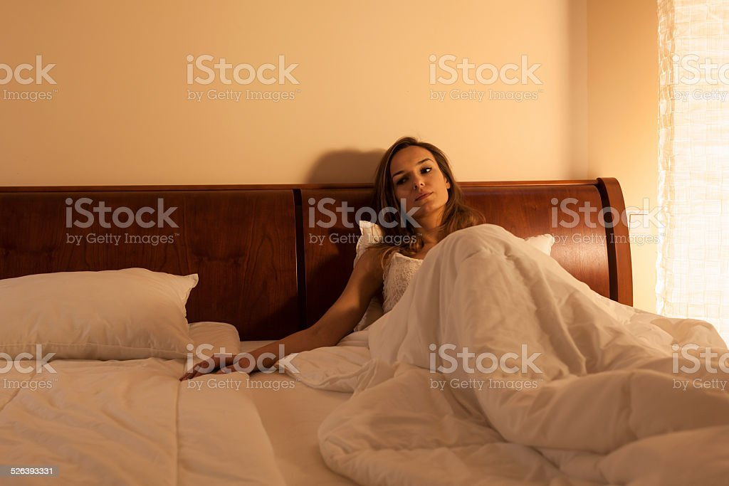 Lonely woman in bed stock photo
