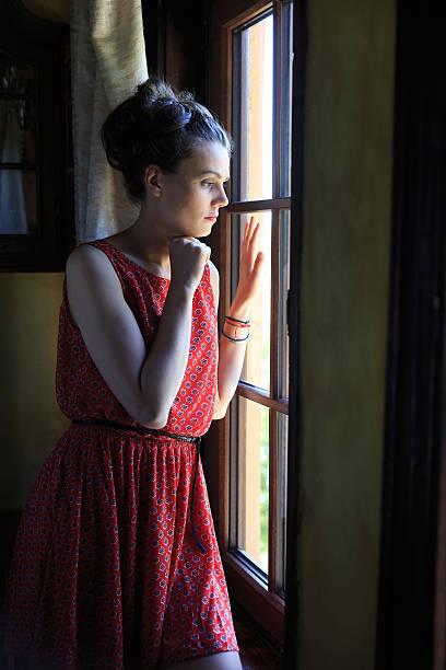 孤独です を見ている女性窓から ストックフォト