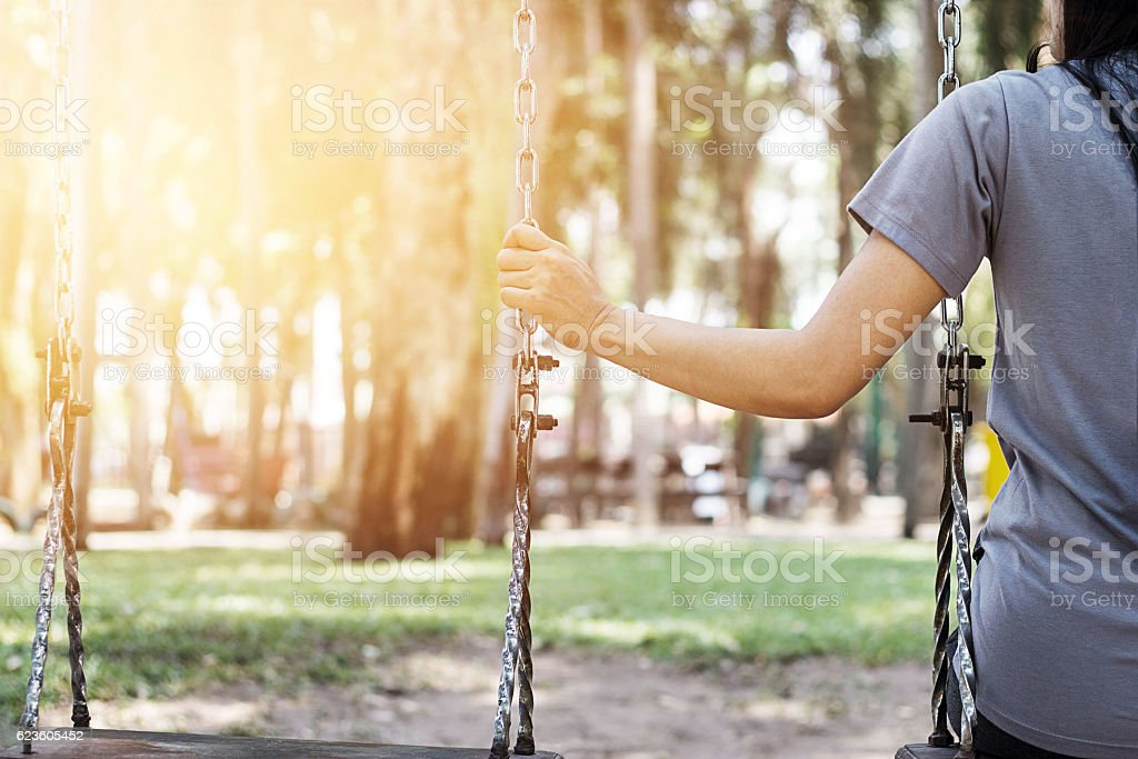 Lonely woman missing her boyfriend while swinging in the park stock photo