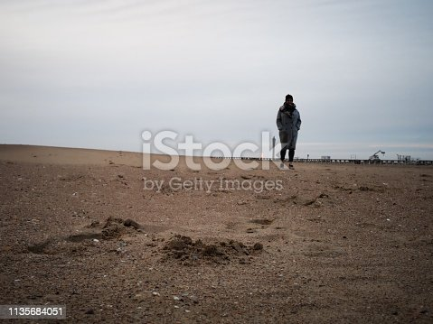 woman in a grey overcoat on a deserted beach in winter, north sea, europe
