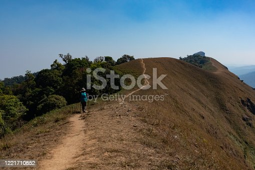 lonely woman walking on mountain top during her journey