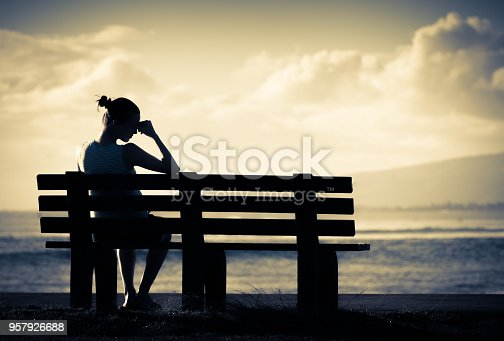 Sad and lonely woman sitting alone on a park bench.