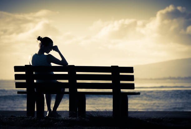 Lonely woman sitting alone on a bench stock photo