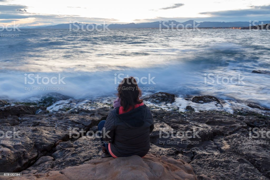 Lonely woman sitting next to the sea stock photo