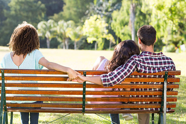 Lonely woman sitting with couple in park stock photo