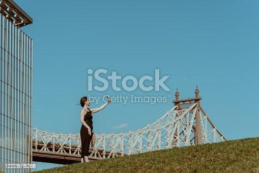 Lonely woman taking selfie on Roosevelt Island