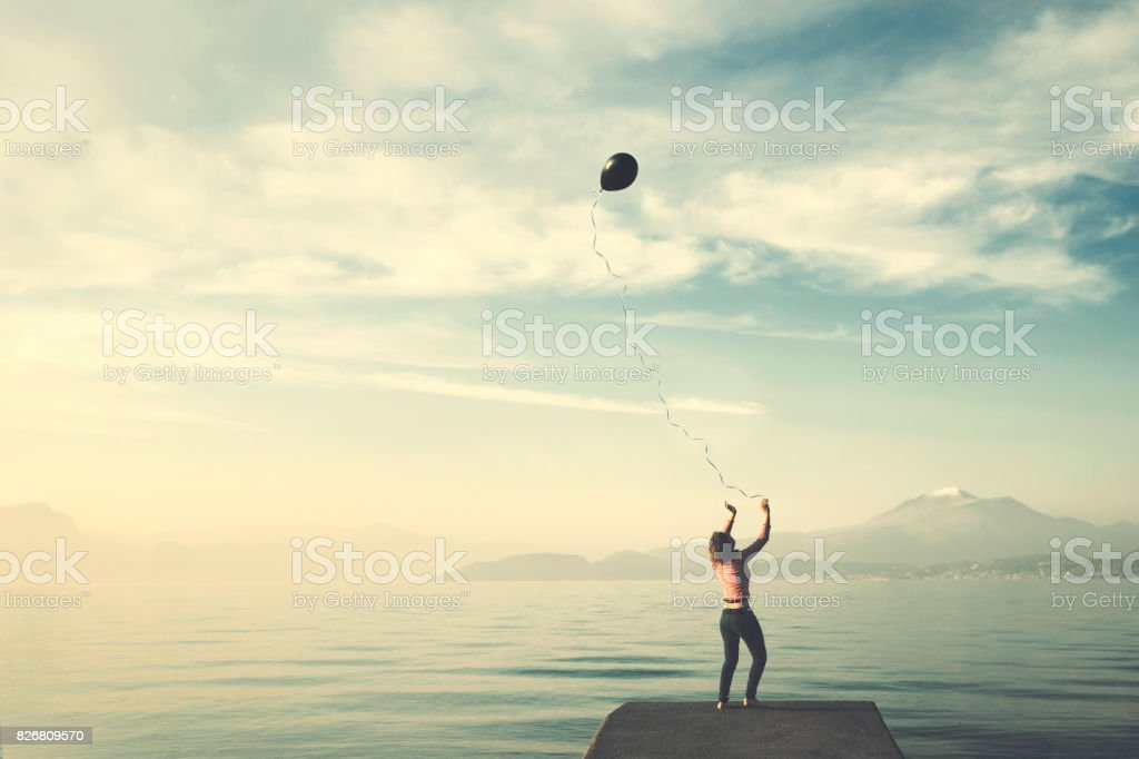 Lonely woman tries to control her balloon that wants to escape to freedom, conceptual image stock photo