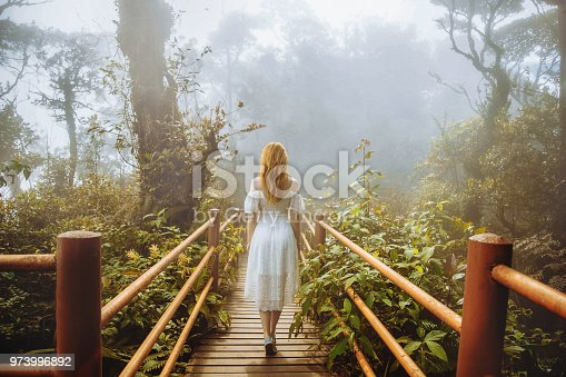 Girl walking on trekking path with railings in tropical forest jungle
