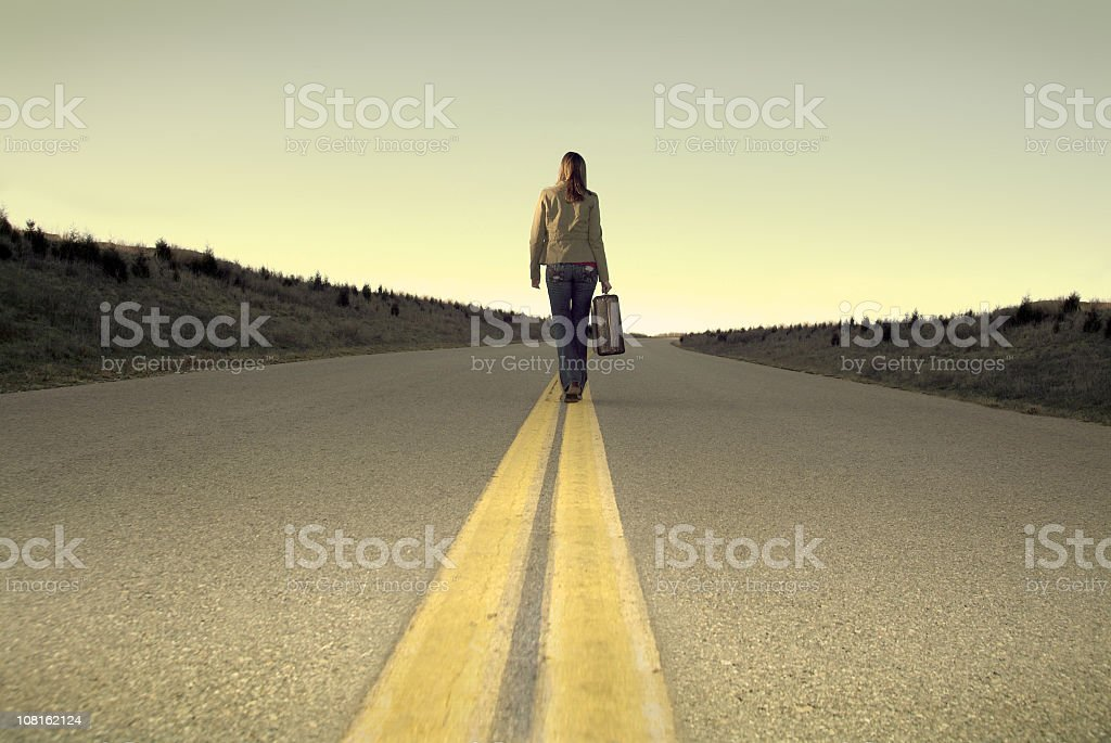 Lonely Woman Walking down the Road with Her Luggage stock photo