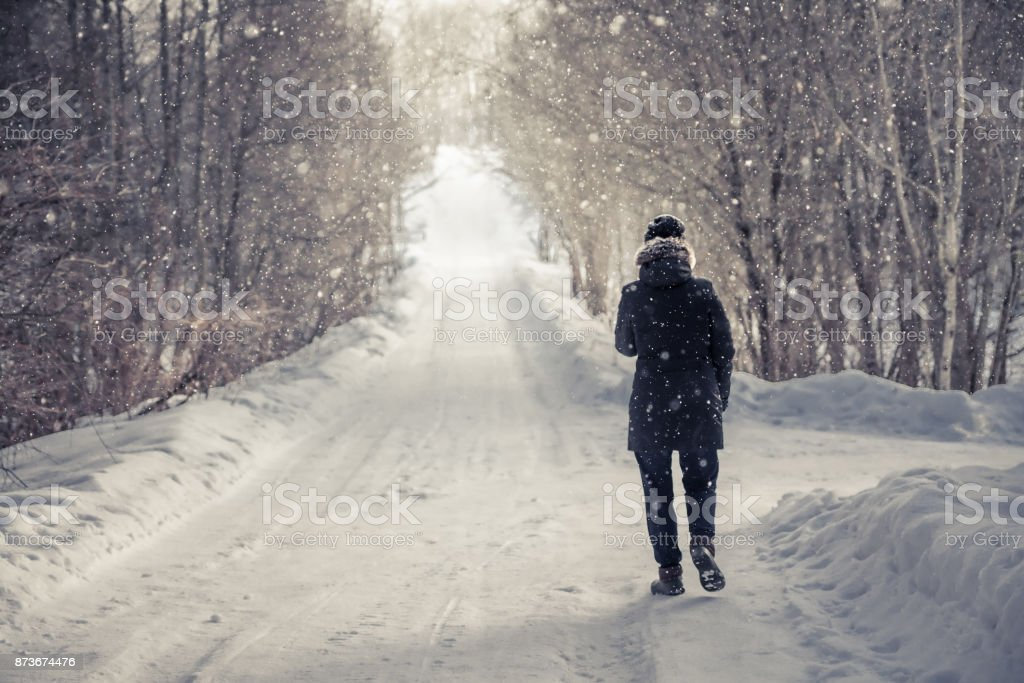 Lonely woman walking on snowy winter road among trees  alley with light at the end of the way in cold winter  day during snowfall  with copy space Single woman walking on snowy winter road among trees  alley with light at the end of the way in cold winter  day during snowfall  with copy space Adult Stock Photo