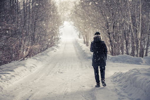 Lonely Woman Walking On Snowy Winter Road Among Trees Alley With Light At The End Of The Way In Cold Winter Day During Snowfall With Copy Space Stock Photo - Download Image Now