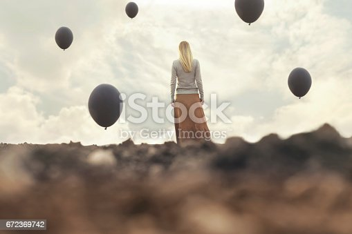 istock lonely woman walking towards infinity in a surreal place 672369742