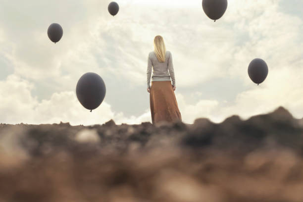 lonely woman walking towards infinity in a surreal place stock photo