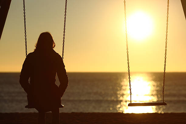 lonely woman watching sunset alone in winter - grief stock photos and pictures