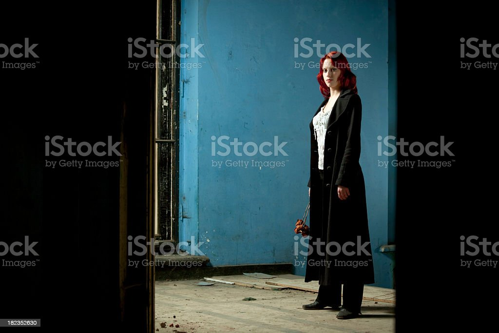 Lonely woman with dry flower standing in old house stock photo