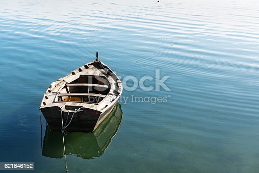 Small wooden fishing boat slowly drifting on the Ria de Pontevedra on a calm Autumn day.