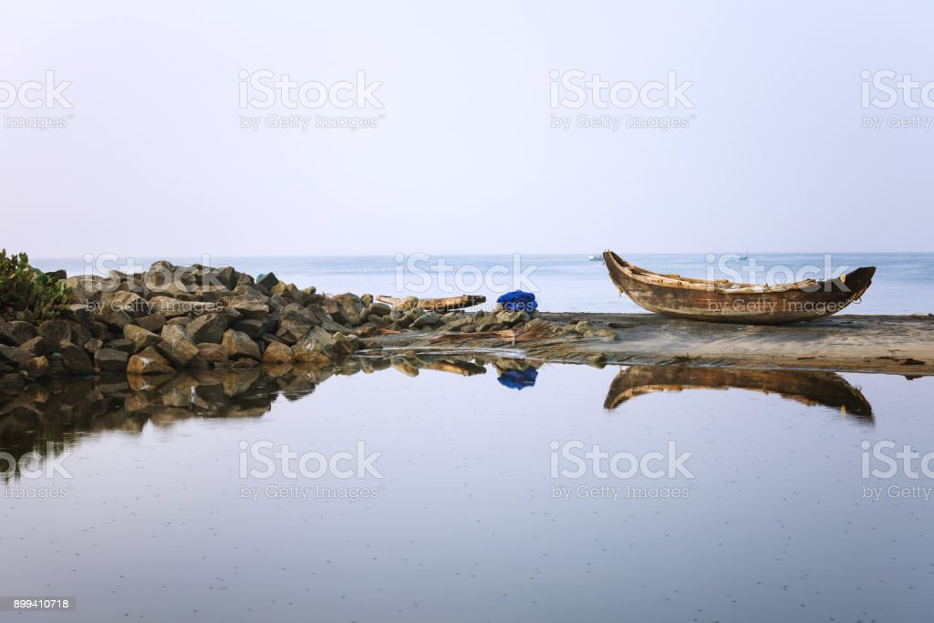 Lonely Wooden fishing boat anchored on the beach sand reflection in backwaters stock photo