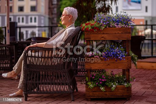 istock lonely wwoman is sitting in the armchair at the cafe with beautiful flowers 1128892474